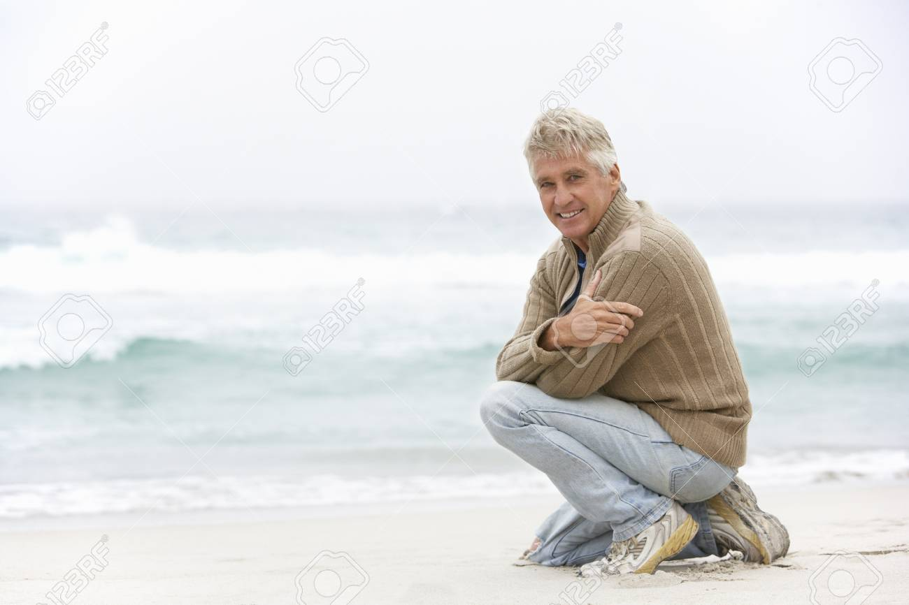Senior Man On Holiday Kneeling On Winter Beach Stock Photo - 8483004