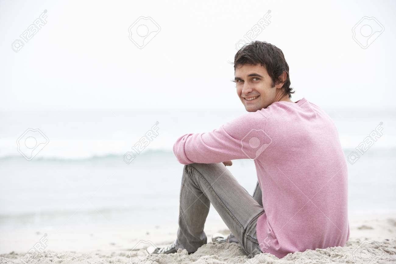 Young Man On Holiday Sitting On Winter Beach Stock Photo - 8482923
