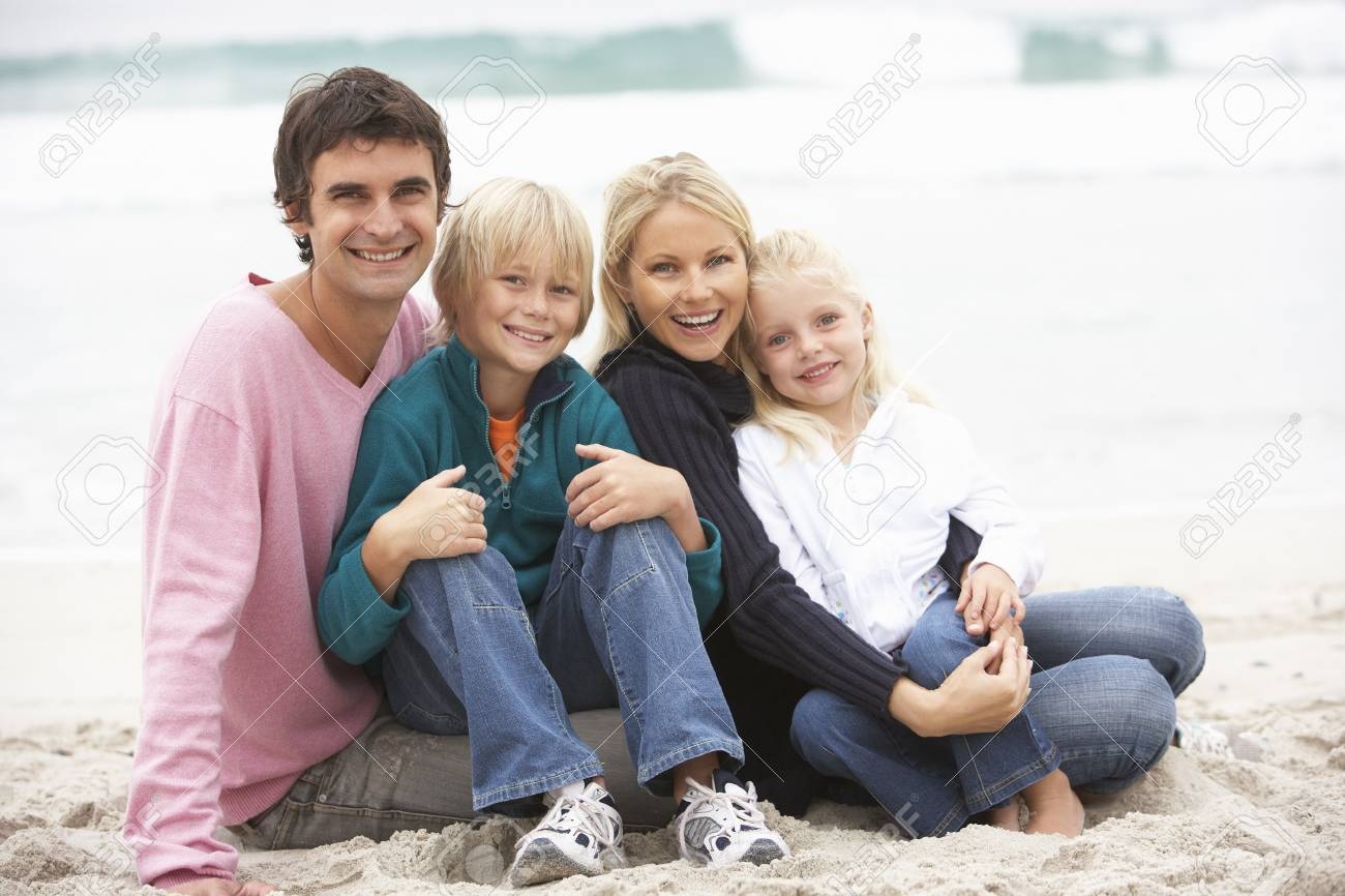 Young Family Sitting On Winter Beach Stock Photo - 8494625