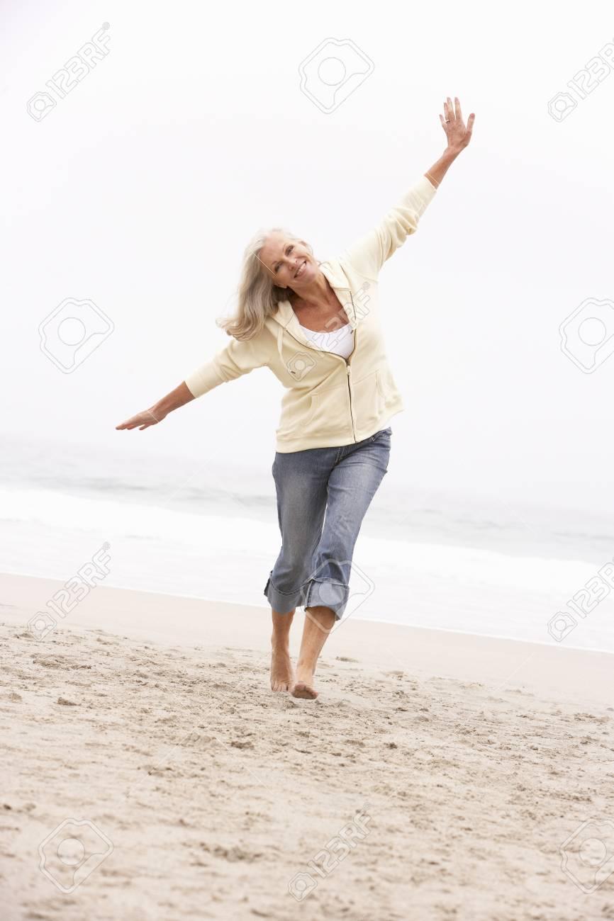 Senior Woman On Holiday Running Along Winter Beach Stock Photo - 8482875
