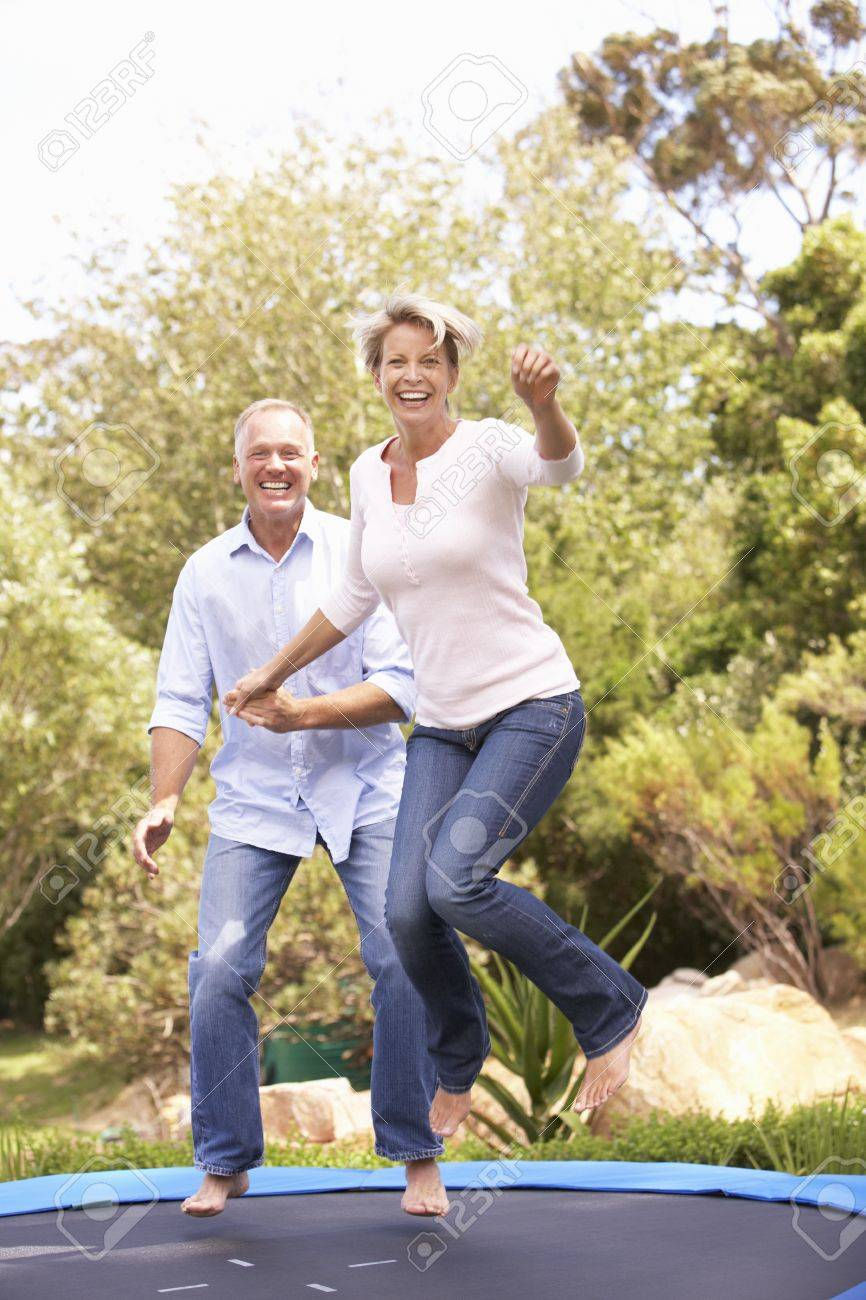 Couple Jumping On Trampoline In Garden Stock Photo - 8483211