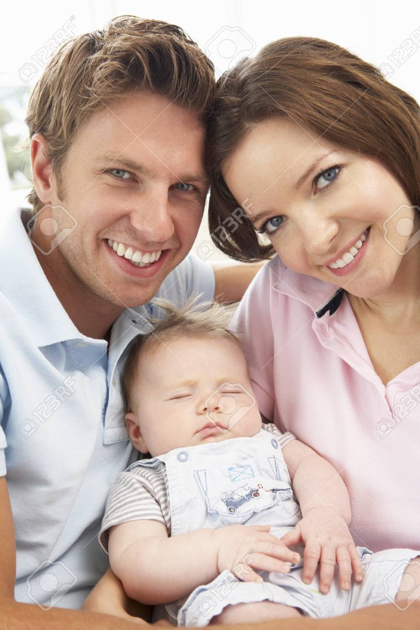 Close up of parents cuddling newborn baby boy at home stock photo 65655914