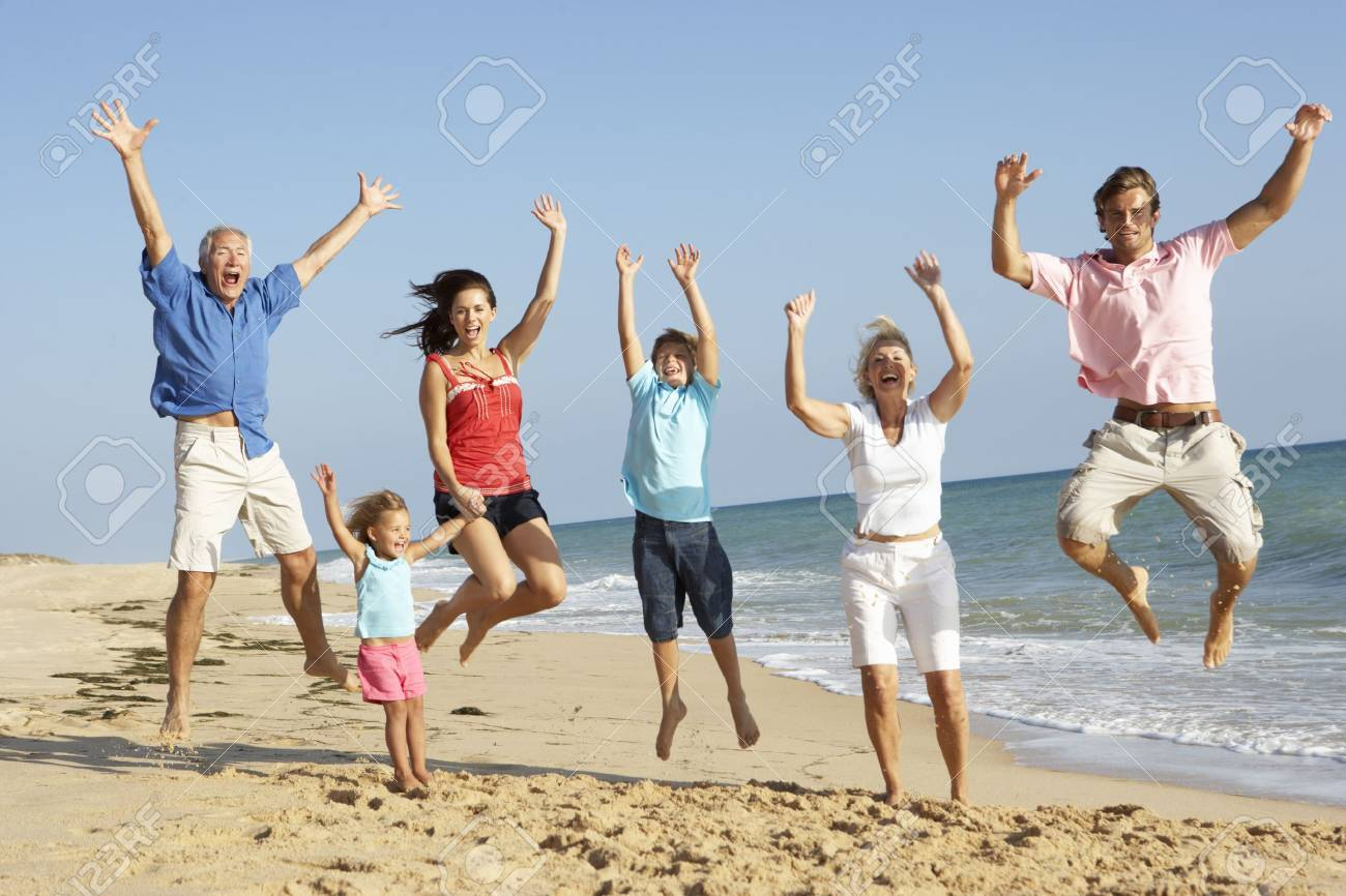 Portrait Of Three Generation Family On Beach Holiday Jumping In Air Standard-Bild - 65656181