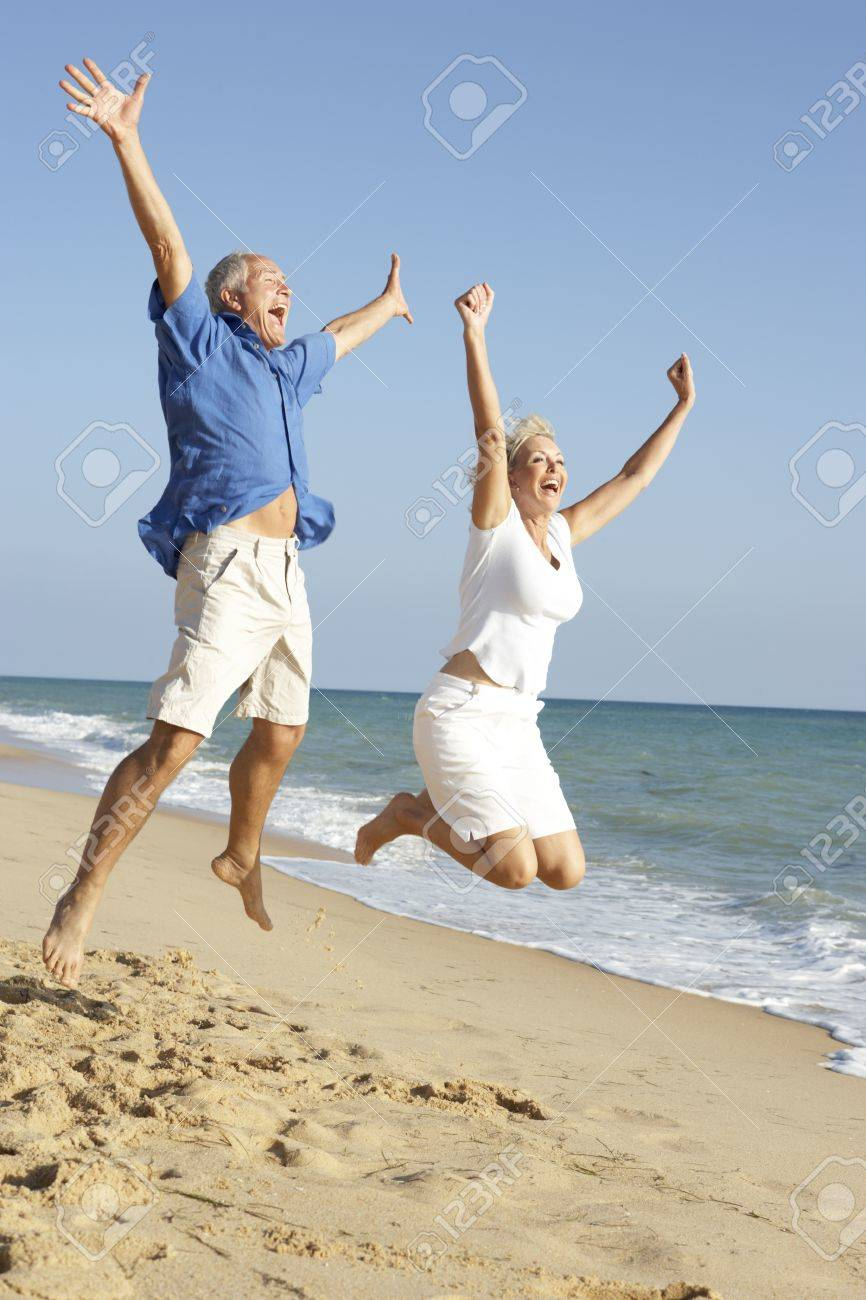 Senior Couple Enjoying Beach Holiday Jumping In Air - 65656177