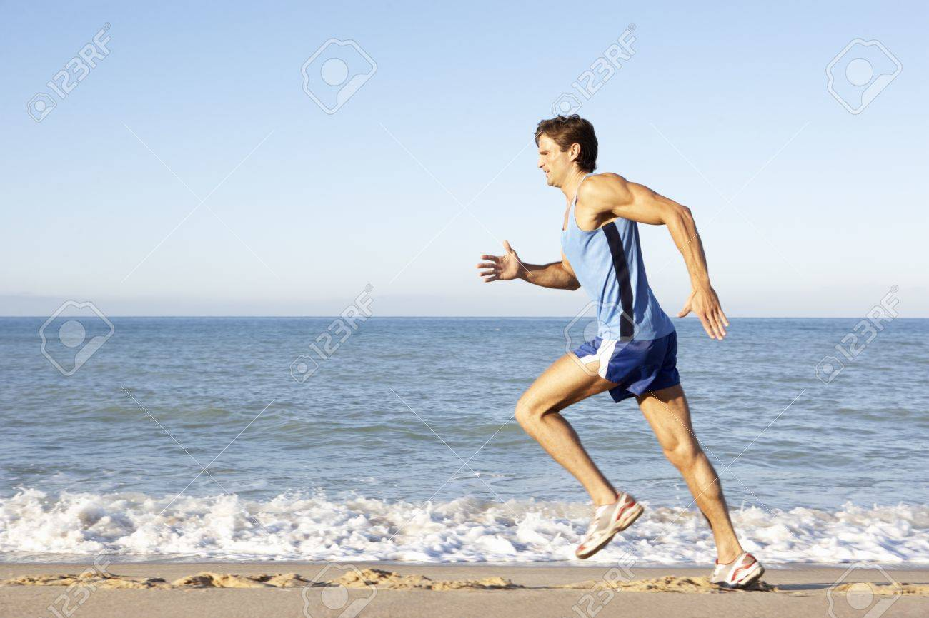 Young Man In Fitness Clothing Running Along Beach Stock Photo - 8503557