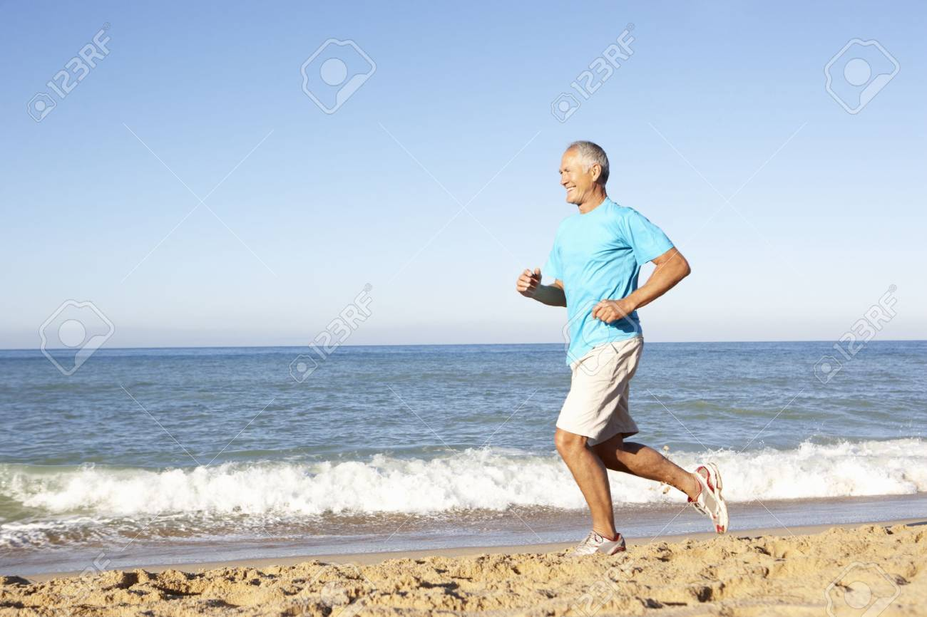 Senior Man In Fitness Clothing Running Along Beach Stock Photo - 8505115