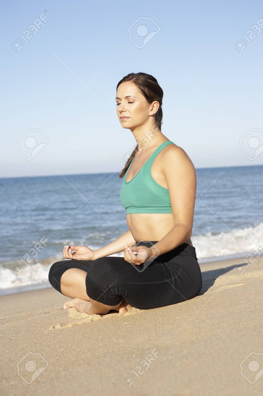 Young Woman In Fitness Clothing Meditating On Beach Stock Photo - 8513851