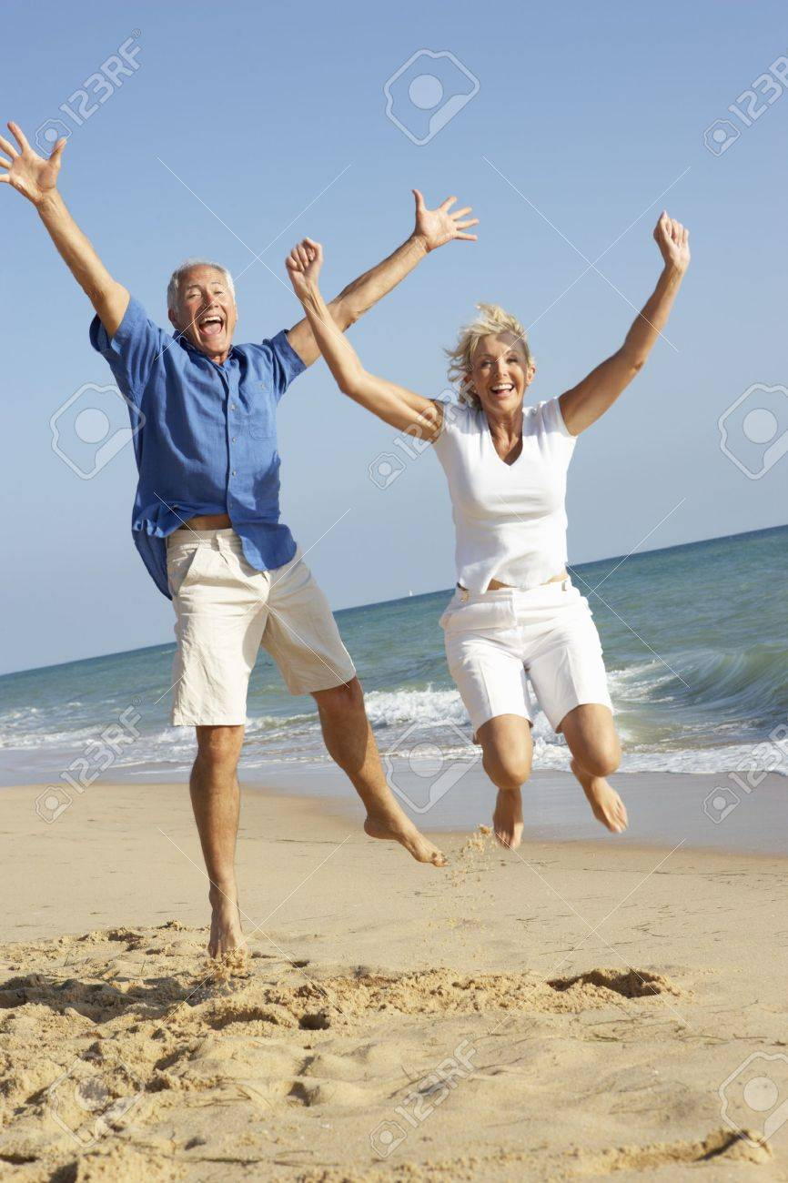 Senior Couple Enjoying Beach Holiday Jumping In Air Stock Photo - 9174767