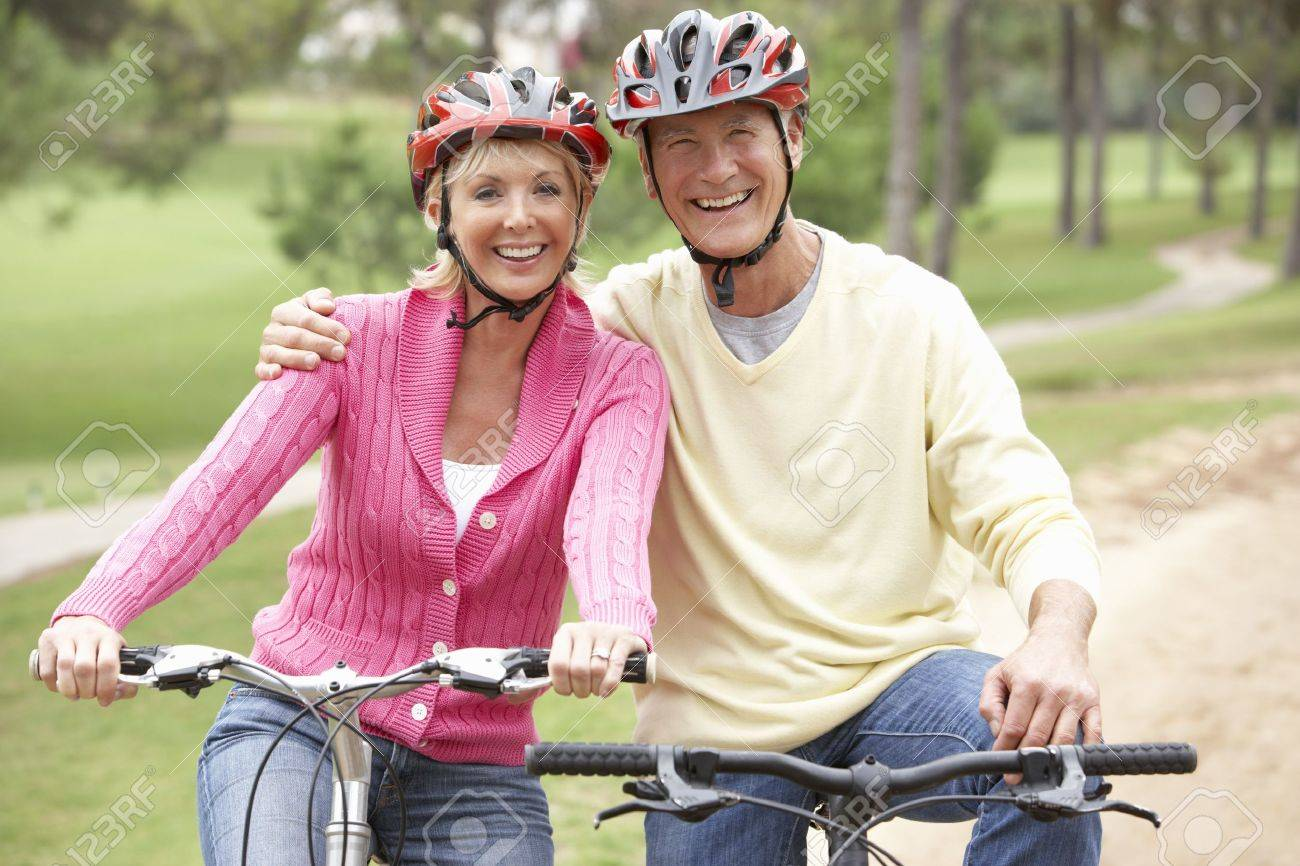Senior couple riding bicycle in park Stock Photo - 9174803