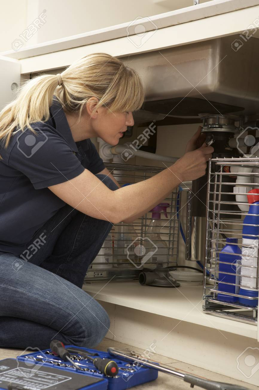 Female Plumber Working On Sink In Kitchen Stock Photo - 9911309