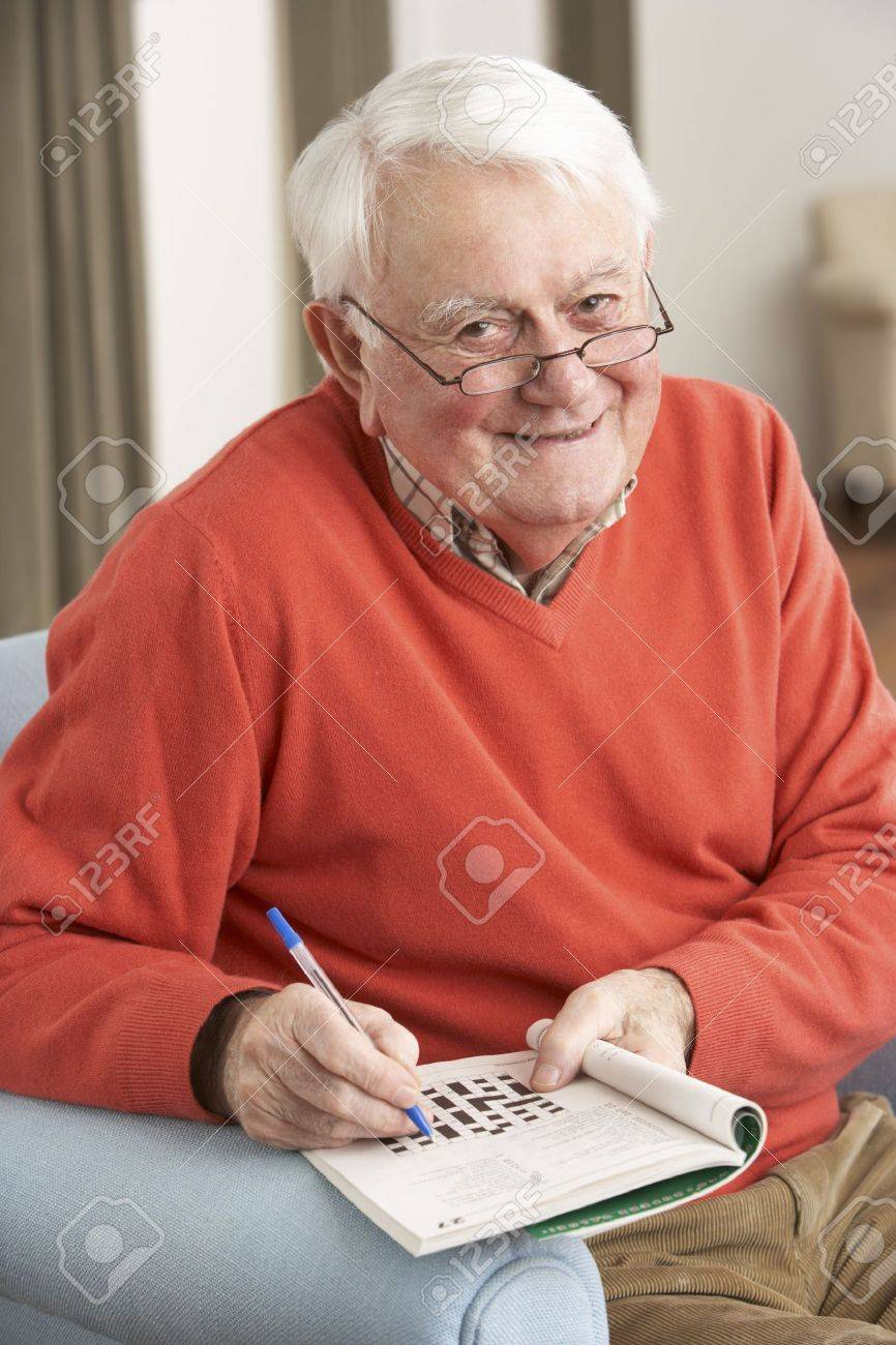 Senior Man Relaxing In Chair At Home Completing Crossword Stock Photo - 9911264
