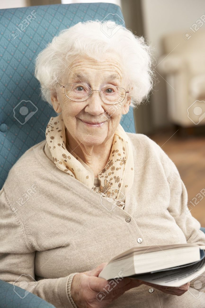 Senior Woman Relaxing In Chair At Home Reading Book Stock Photo - 9911174