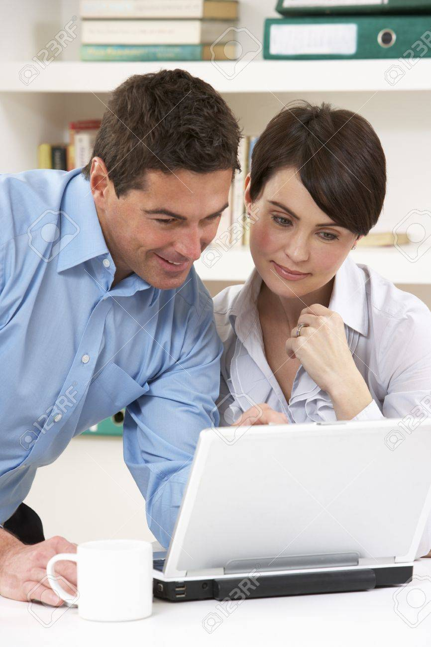 Couple Working From Home Using Laptop Stock Photo - 9911385