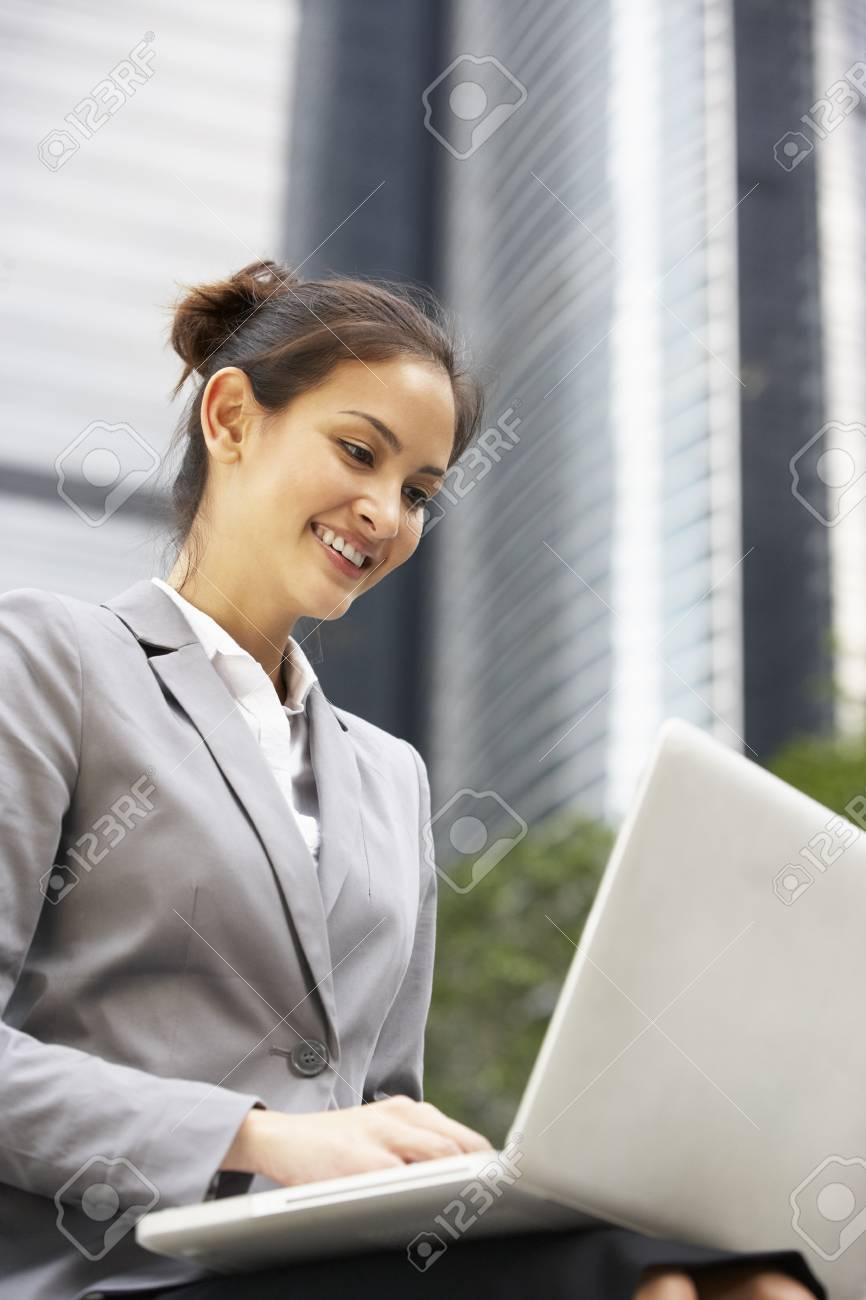 Hispanic Businesswoman Working On Laptop Outside Office Stock Photo - 18709788