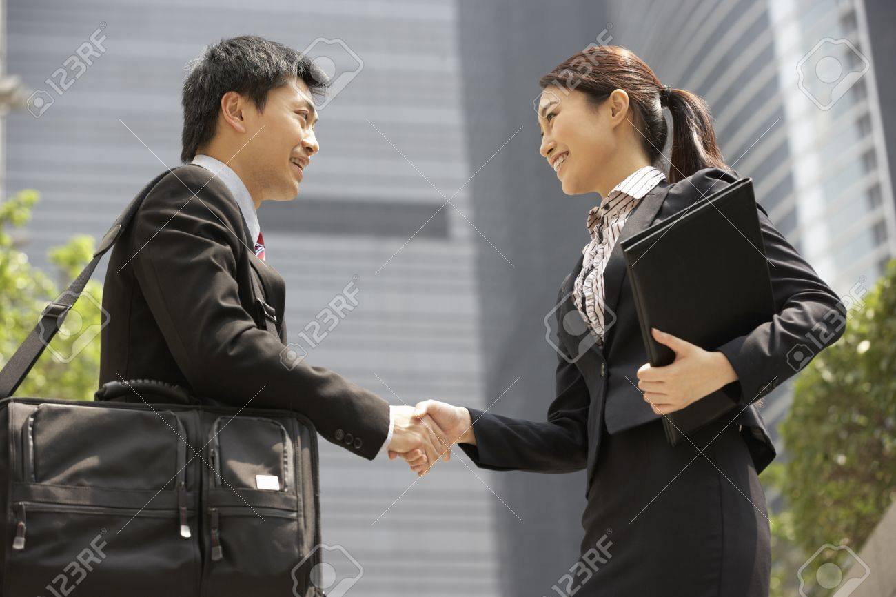 Chinese Businessman And Businesswoman Shaking Hands Outside Office Stock Photo - 18709708