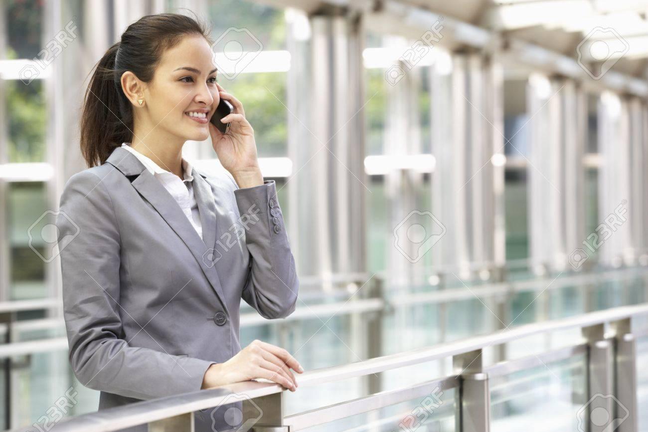 Hispanic Businesswoman Outside Office On Mobile Phone Stock Photo - 18709486