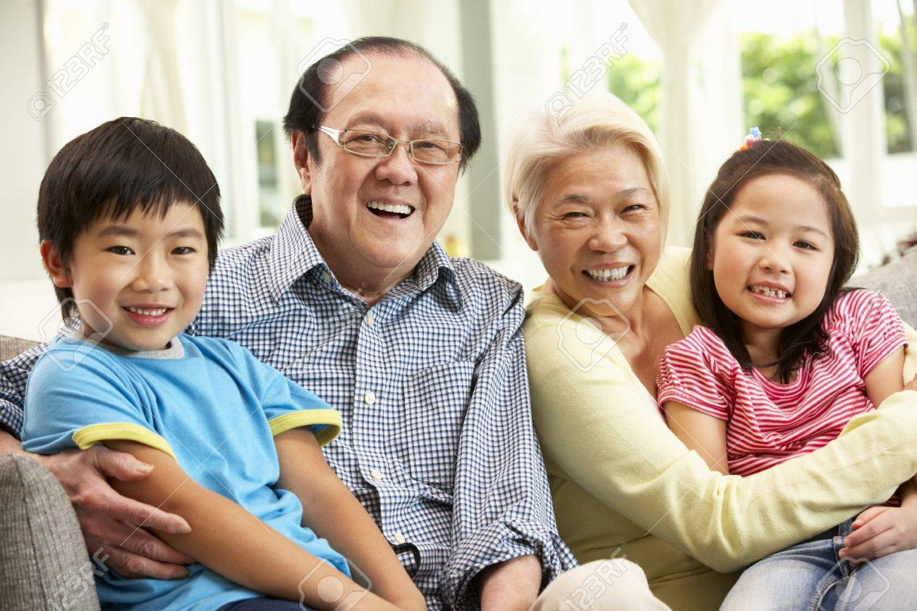 Portrait Of Chinese Grandparents With Grandchildren Relaxing At Home Together Stock Photo - 18710601