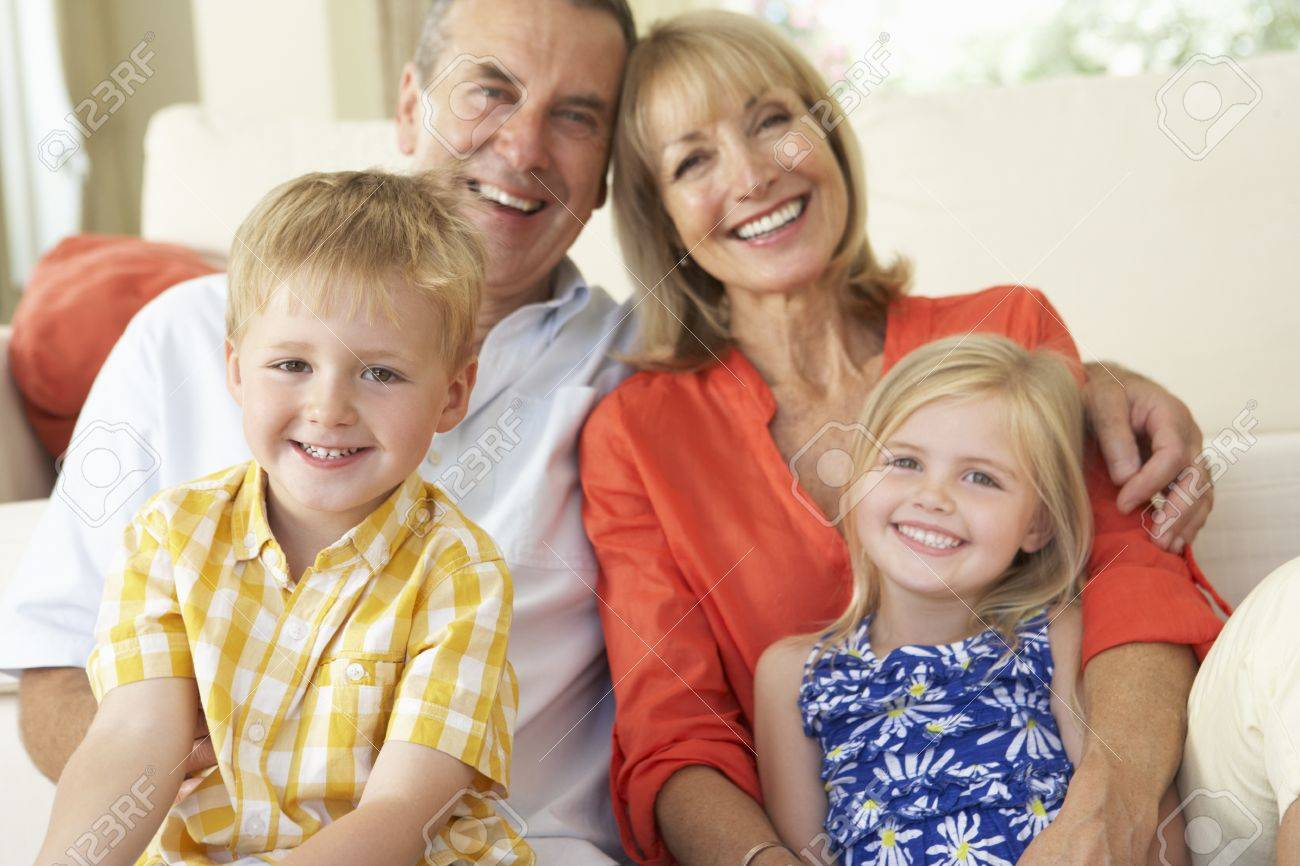 Grandparents With Grandchildren Relaxing On Sofa At Home Stock Photo - 18720838