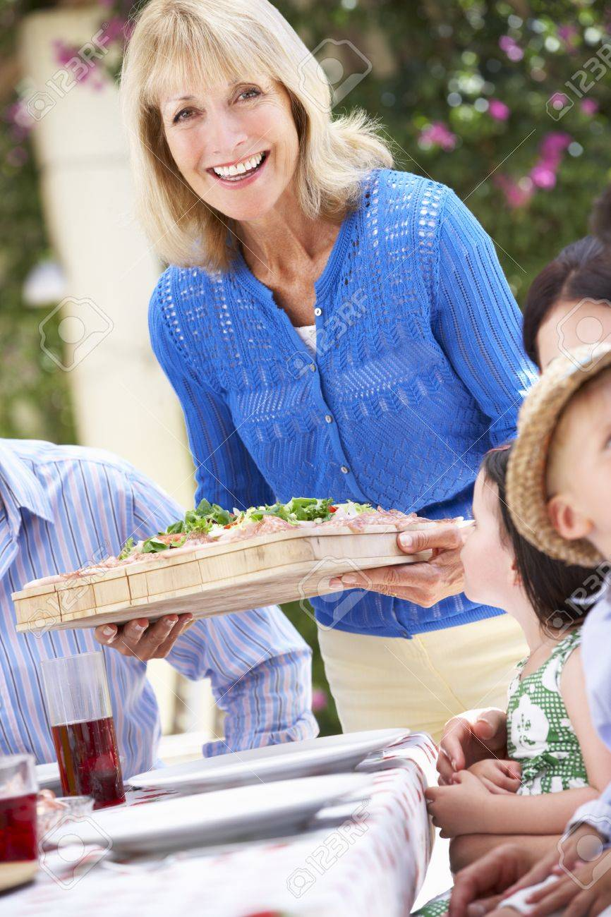 Senior Woman Serving At Multi Generation Family Meal Stock Photo - 18723069