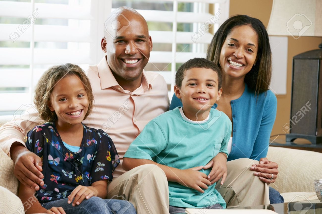 Portrait Of Family Sitting On Sofa Together Stock Photo - 18735759