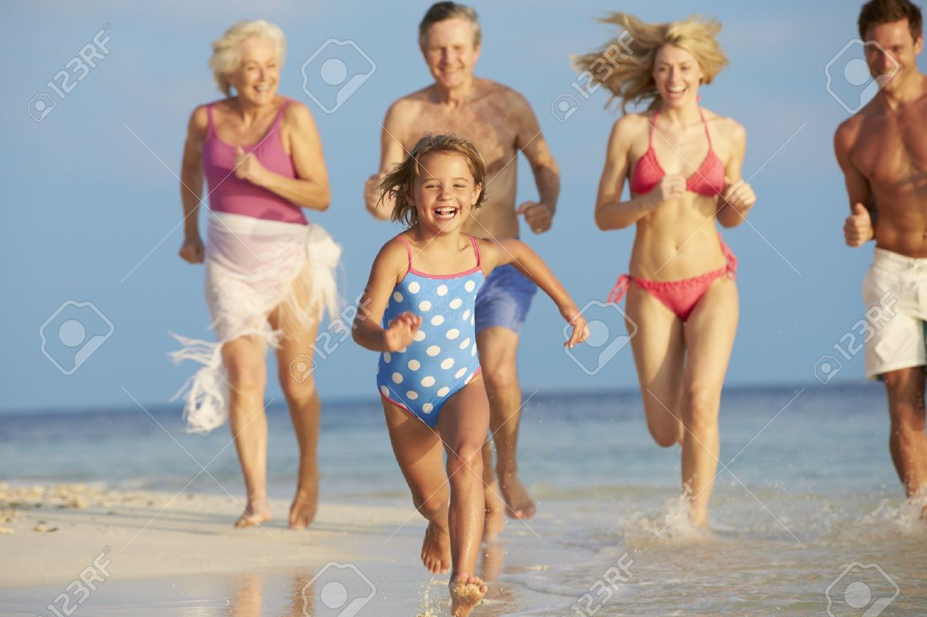 Multi Generation Family Having Fun In Sea On Beach Holiday Stock Photo - 19530289