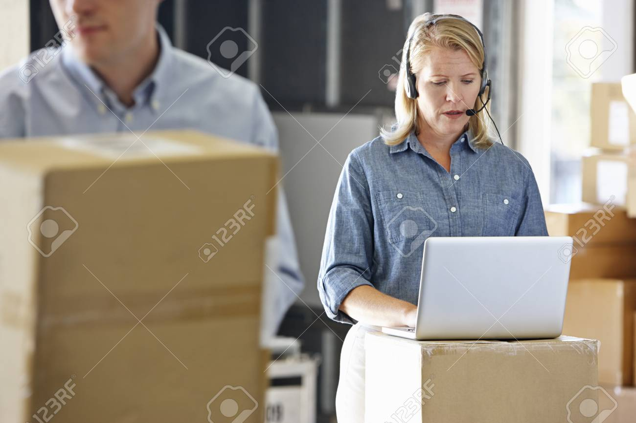 Female Manager Using Headset In Distribution Warehouse Stock Photo - 19530525