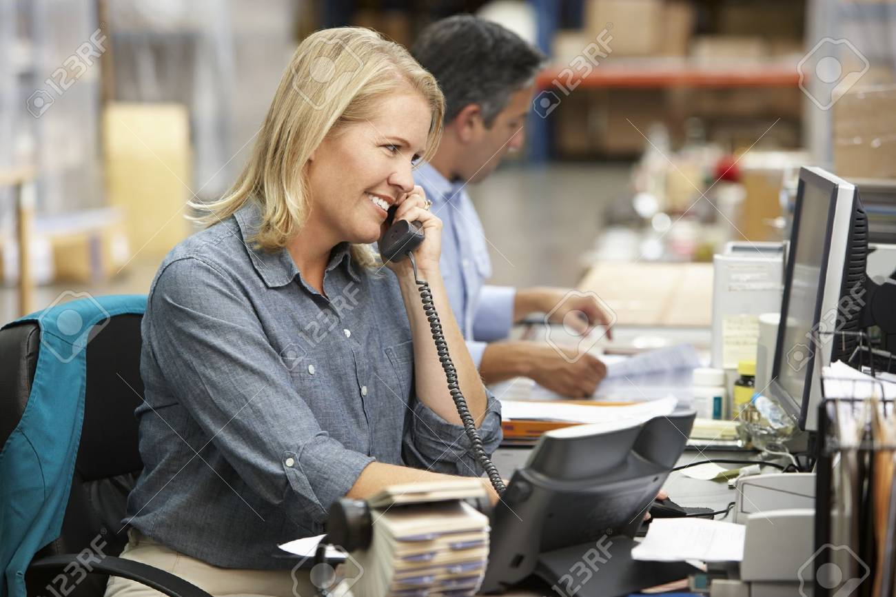 Businesswoman Working At Desk In Warehouse Stock Photo - 19530741
