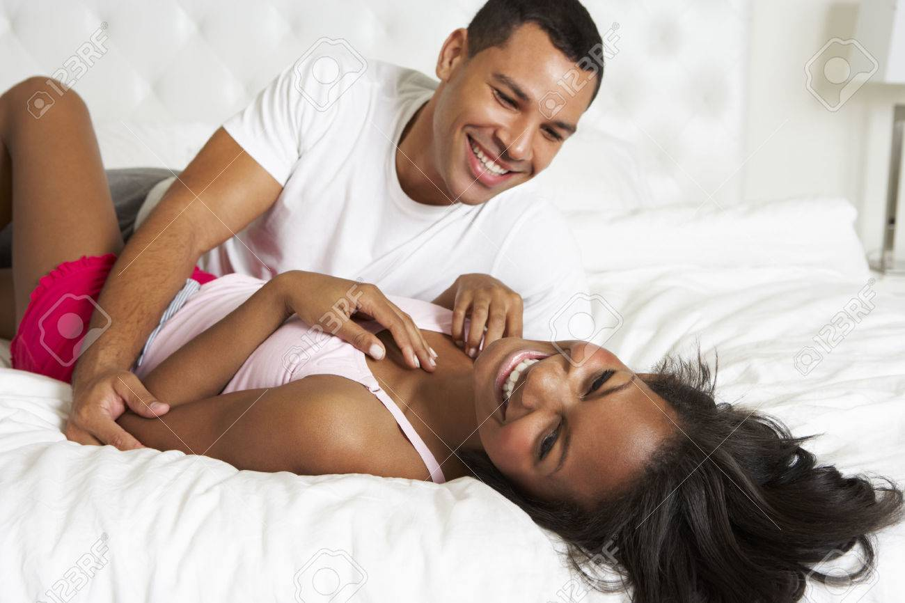 Couple Relaxing In Bed Wearing Pajamas Stock Photo - 24446312