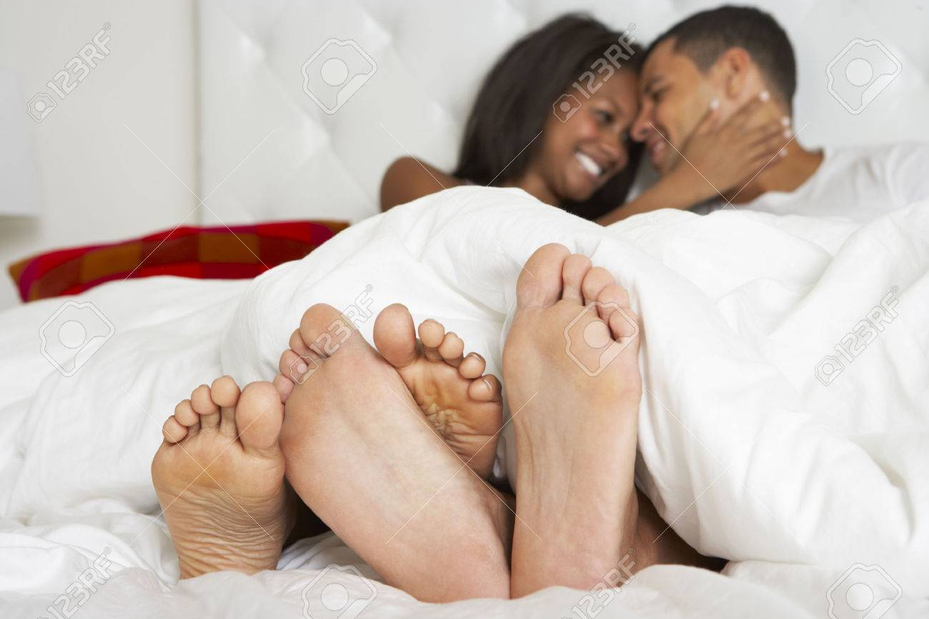 Couple Relaxing In Bed Wearing Pajamas Stock Photo - 24446326