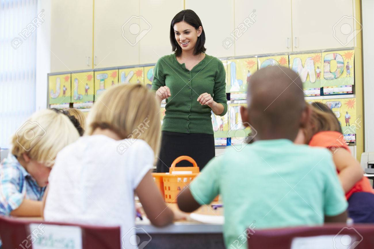 teacher talking to elementary pupils in classroom stock photo
