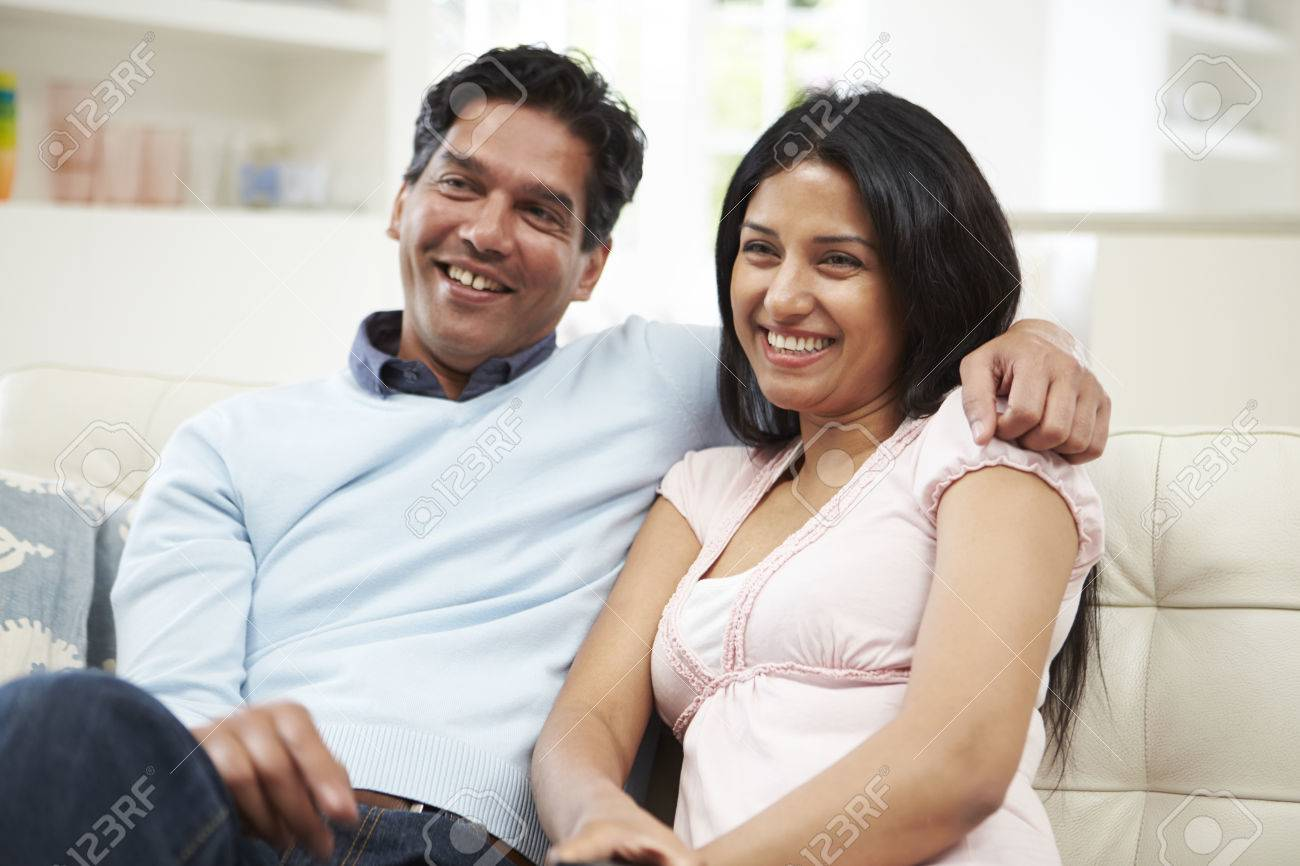 Indian Couple Sitting On Sofa Watching TV Together Stock Photo - 24508167