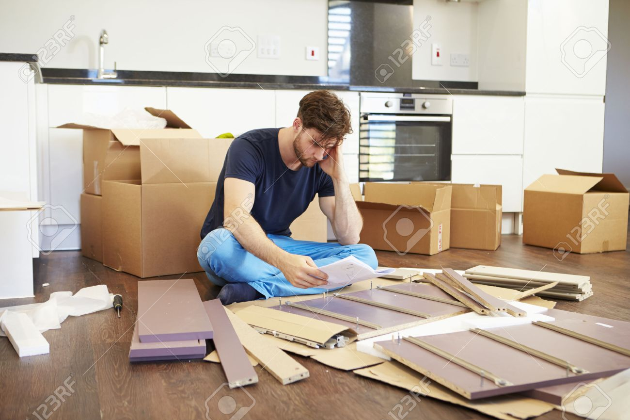 Frustrated Man Putting Together Self Assembly Furniture Stock Photo    31009837