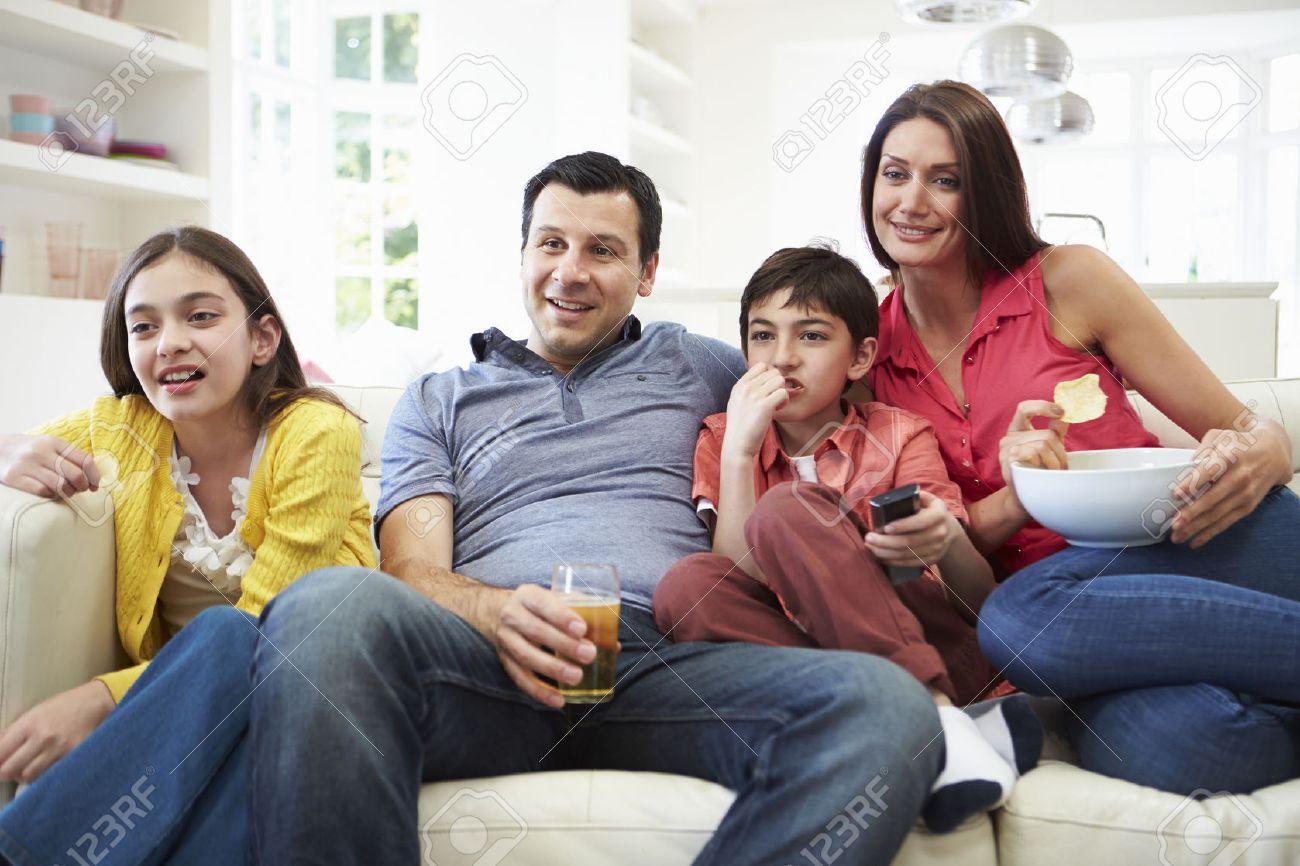 Hispanic Family Sitting On Sofa Watching Tv Together Stock Photo