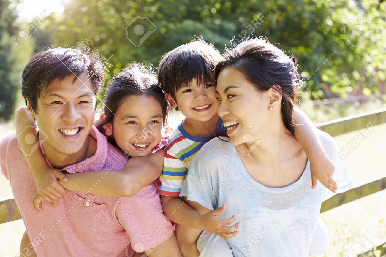 Asian Family Enjoying Walk In Summer Countryside Stock Photo - 31047348