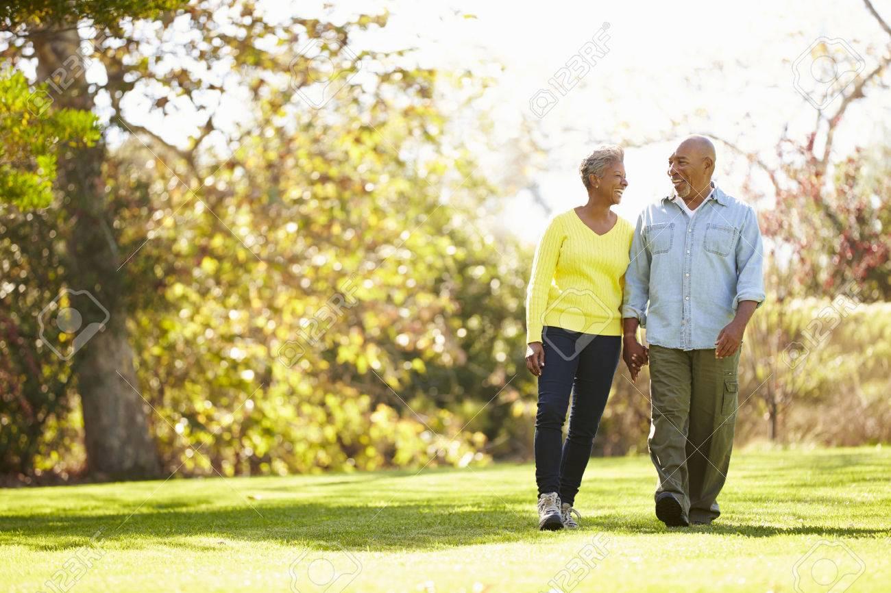 Senior Couple Walking Through Autumn Woodland - 31053828