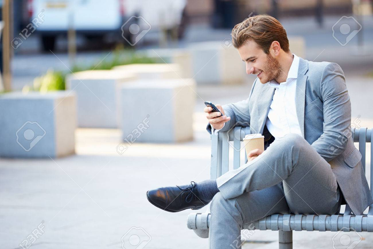 Businessman On Park Bench With Coffee Using Mobile Phone - 31066064