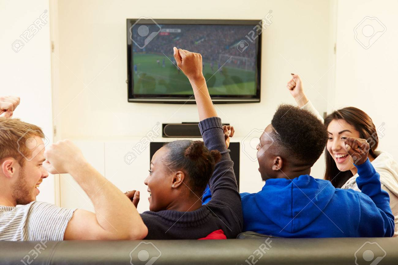 Two Young Couples Watching Television At Home Together - 31066394