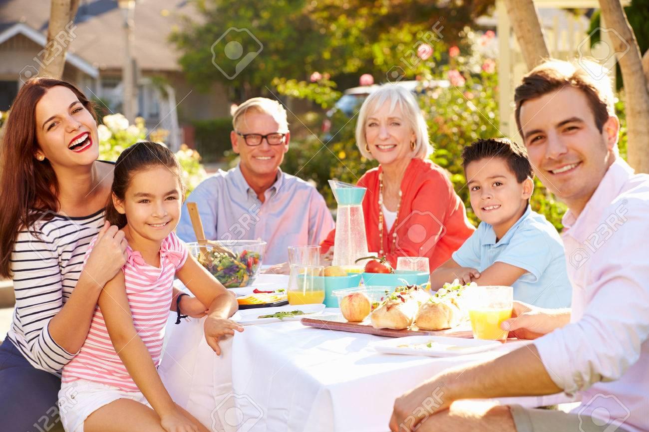 Multi-Generation Family Enjoying Outdoor Meal In Garden - 31065797