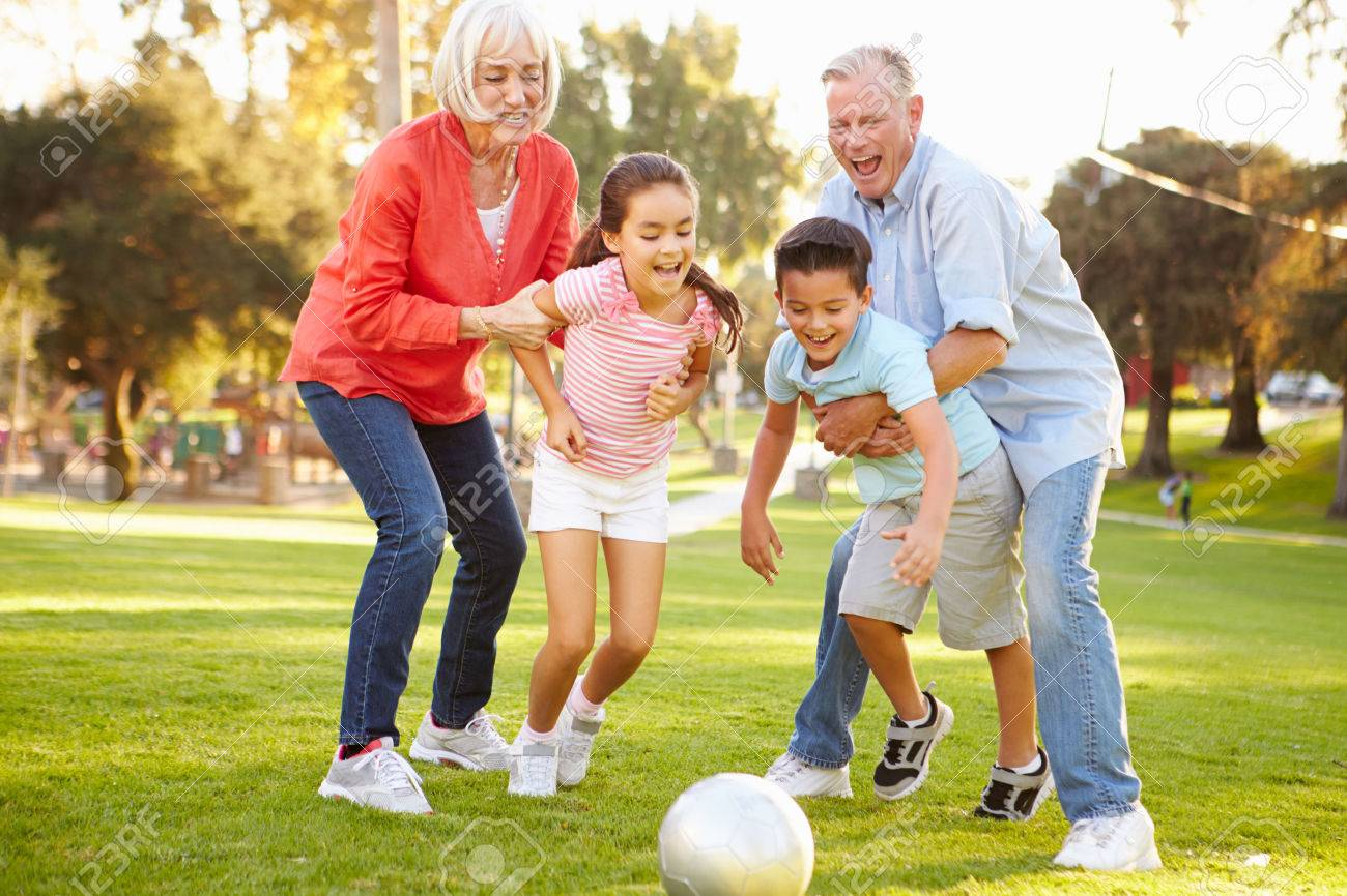 Grandson: Grandparents Playing Soccer With Grandchildren In Park Buying  Stock