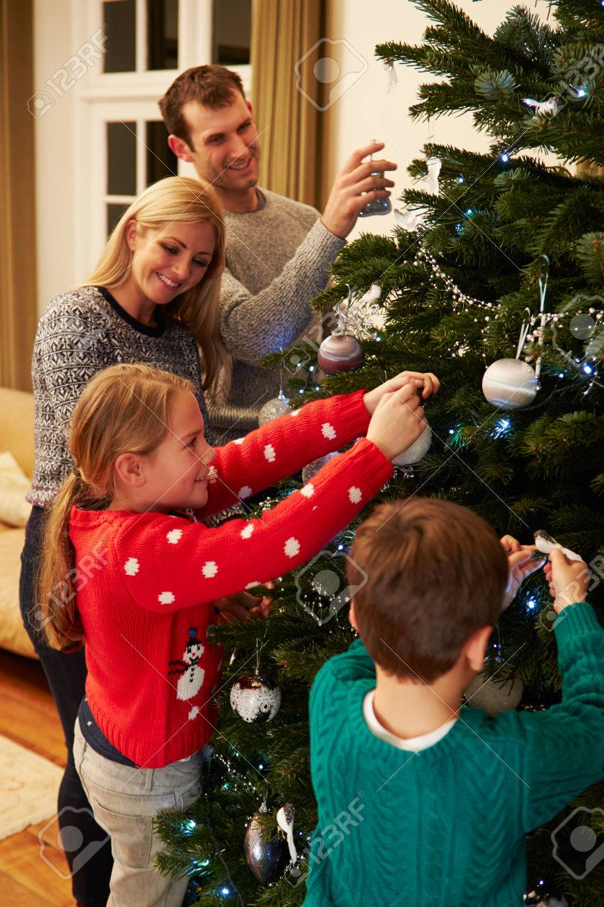 Family Decorating Christmas Tree At Home Together Stock Photo ...
