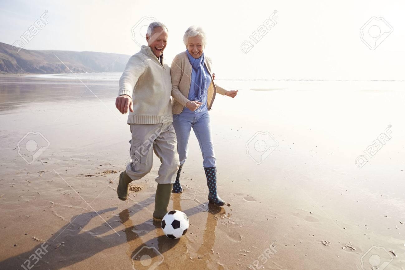 Senior Pareja Jugando Al Futbol En La Playa De Invierno Fotos