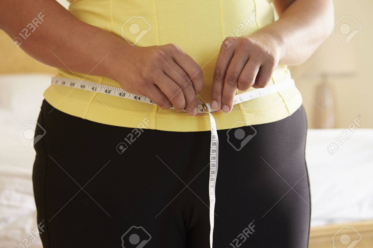 Close Up Of Overweight Woman Measuring Waist - 33519172