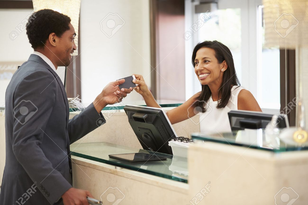 businessman checking in at hotel reception front desk stock photo businessman checking in at hotel reception front desk stock photo 33546014