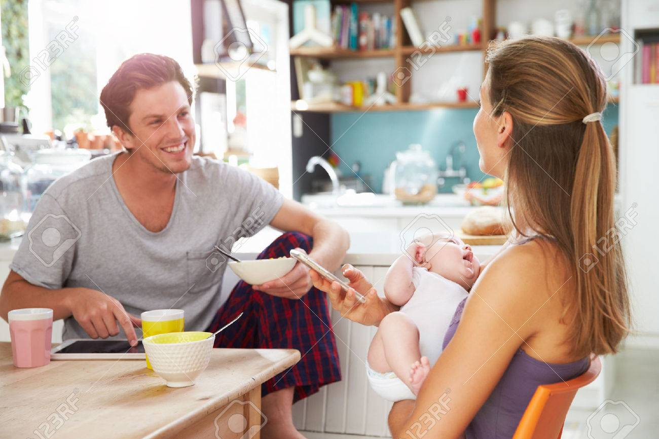 Family With Baby Girl Use Digital Devices At Breakfast Table - 41142241