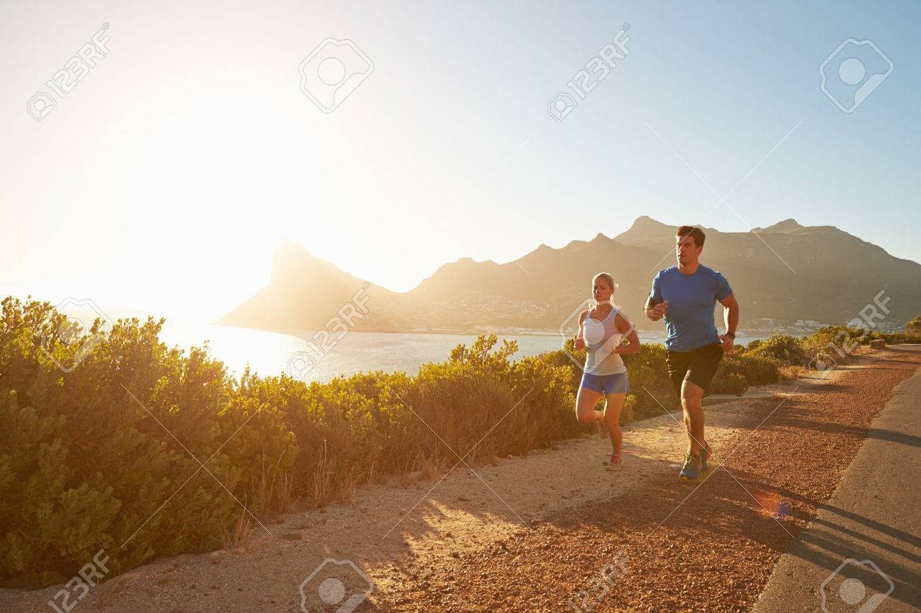 Man and woman running together on an empty road - 41392792