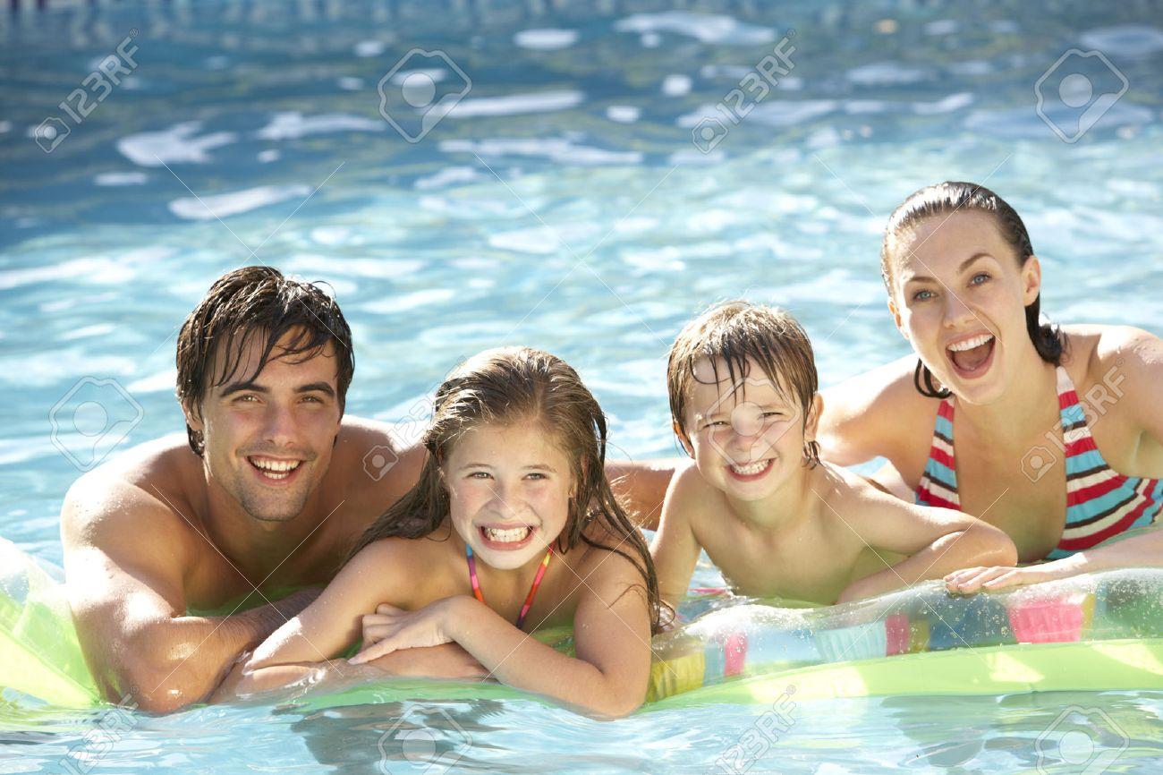 nudism swimmingpool swimming pool family: Young Family Relaxing In Swimming Pool