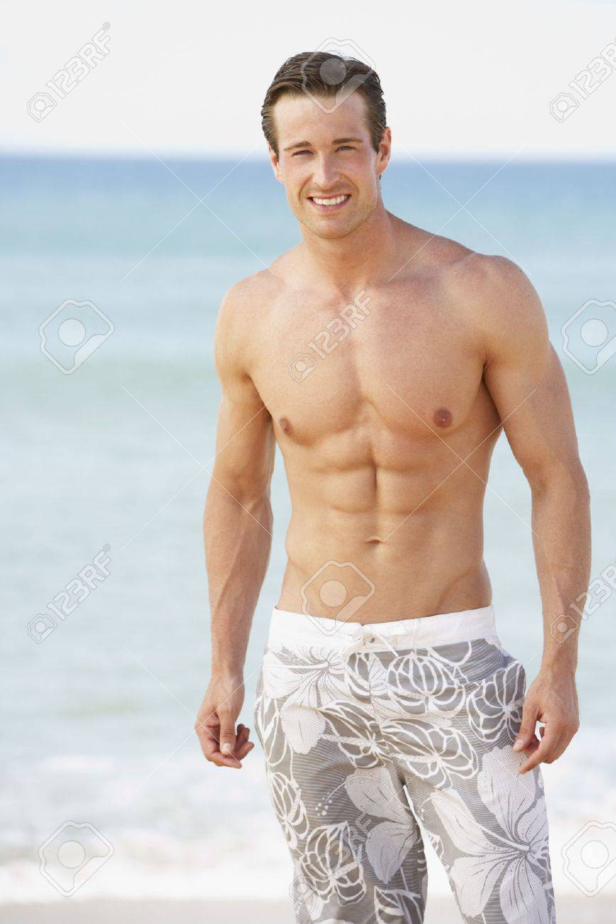 e453bd557b0 Young Man Wearing Swimming Costume Standing On Beach Stock Photo ...