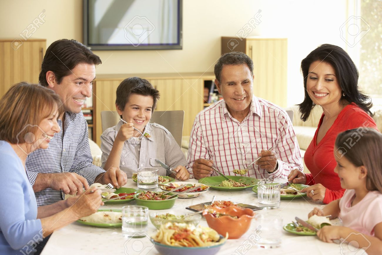 Extended Hispanic Family Enjoying Meal At Home Stock Photo