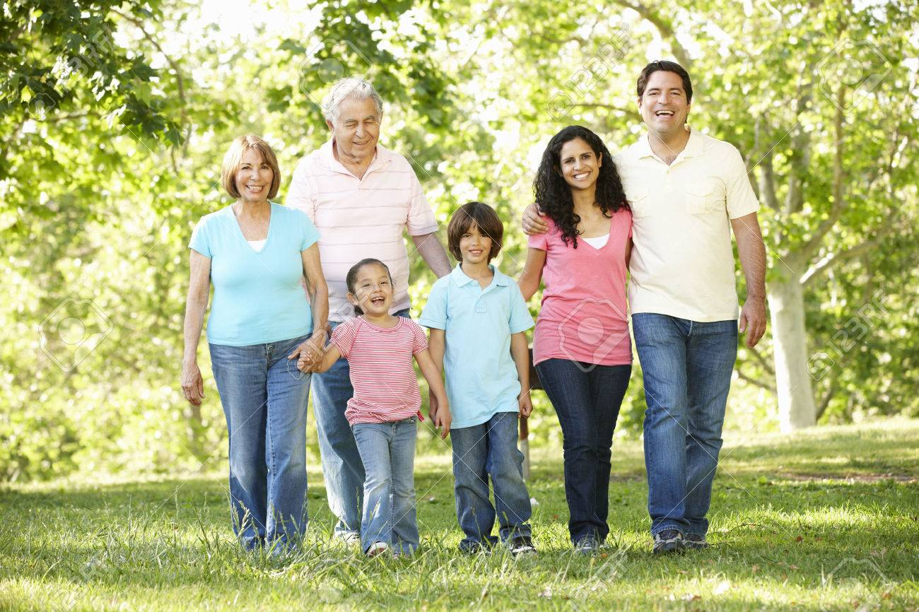 Multi Generation Hispanic Family Walking In Park Stock Photo