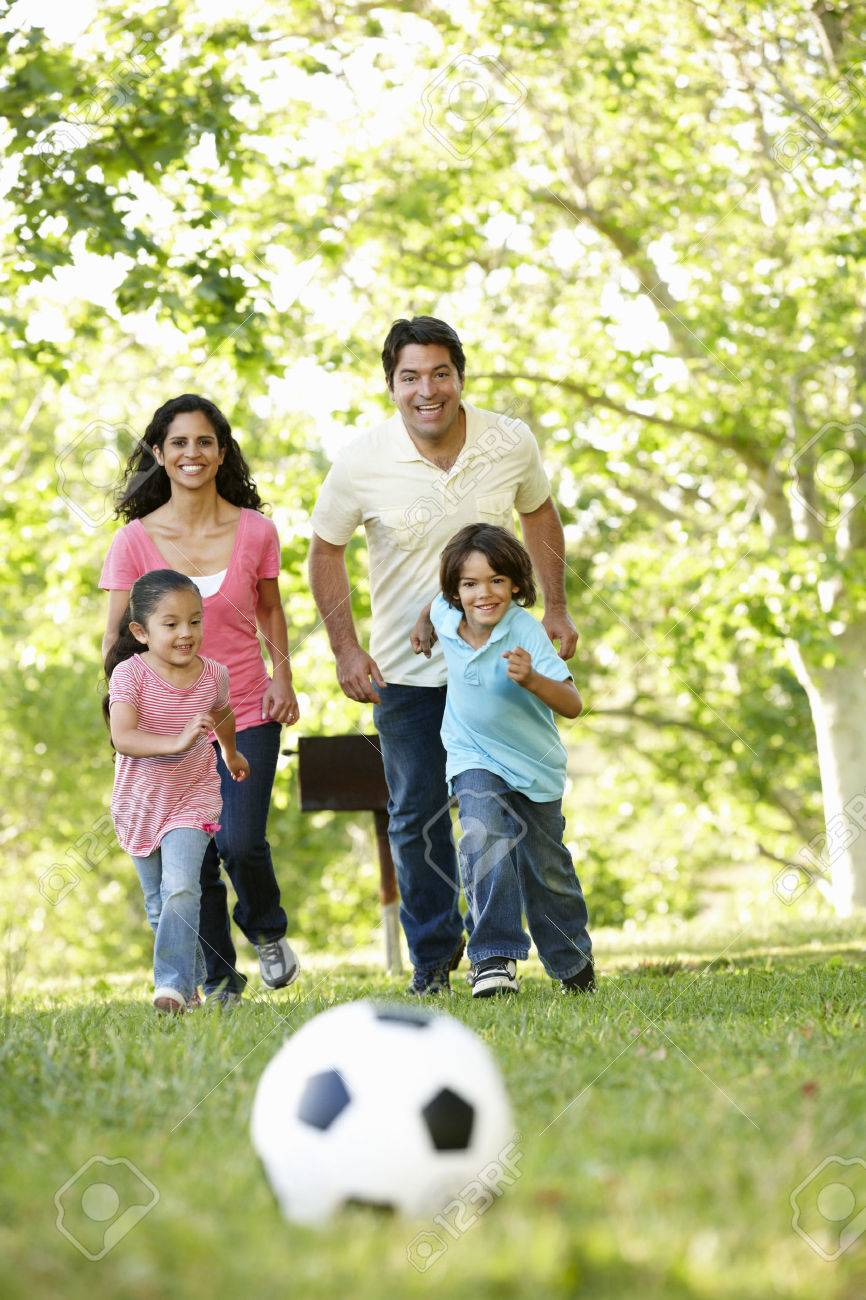 Young Hispanic Family Playing Football In Park Stock Photo